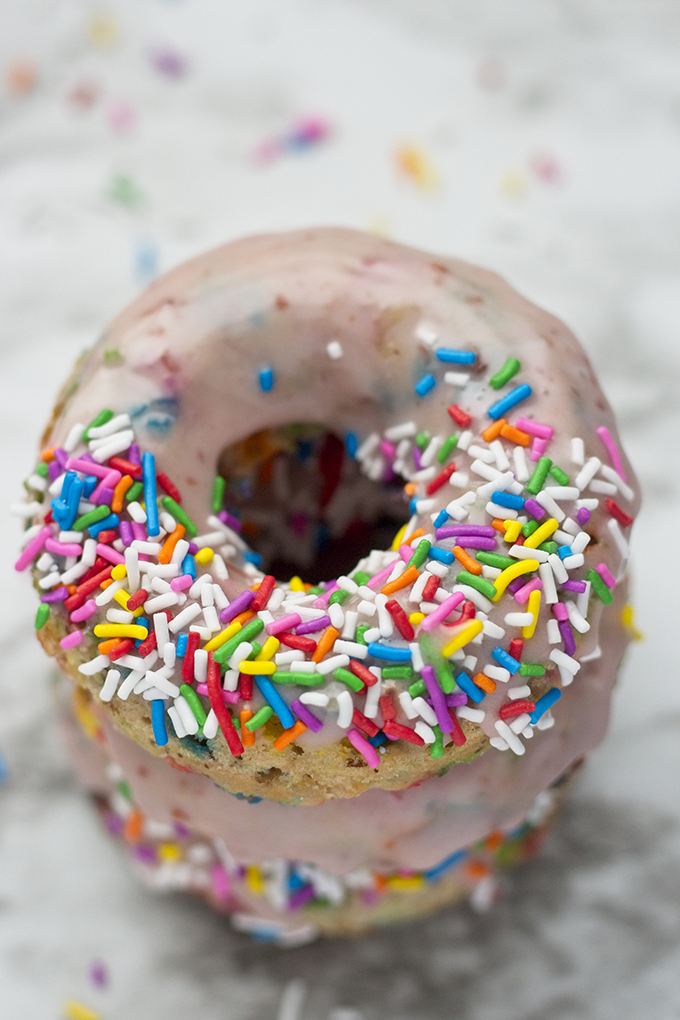These Vegan Funfetti Donuts are studded with rainbow sprinkles and topped with a sweet pink glaze! This is an easy recipe full of fun!